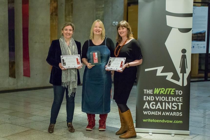 3 women standing next to a WritetoEndVAW banner