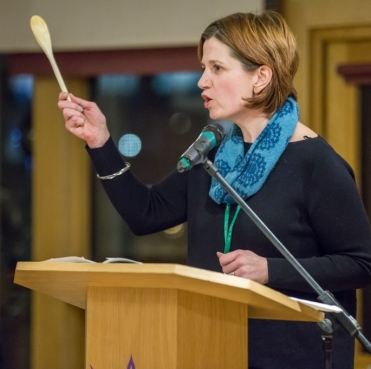 A picture of a woman speaking at a podium and waving a wooden spoon